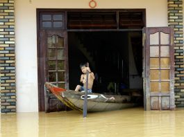 Boy maneuvering boat out of a flooded house in Vietnam (© AP Images)