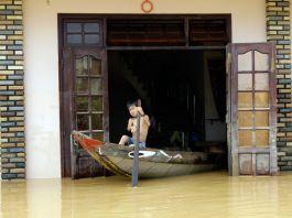 ویت نام میں ایک لڑکا سیلابی پانی سے بھرے اپنے گھر سے کشتی میں بیٹھ کر نکل رہا ہے۔ (© AP Images)