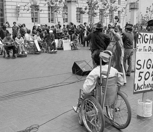Sebuah demonstrasi di luar gedung kantor federal di San Francisco, selama pendudukan oleh aktivis hak-hak penyandang cacat pada tahun 1977 (© AP Images)
