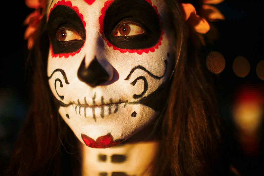 Woman with elaborate face painting (© AP Images)