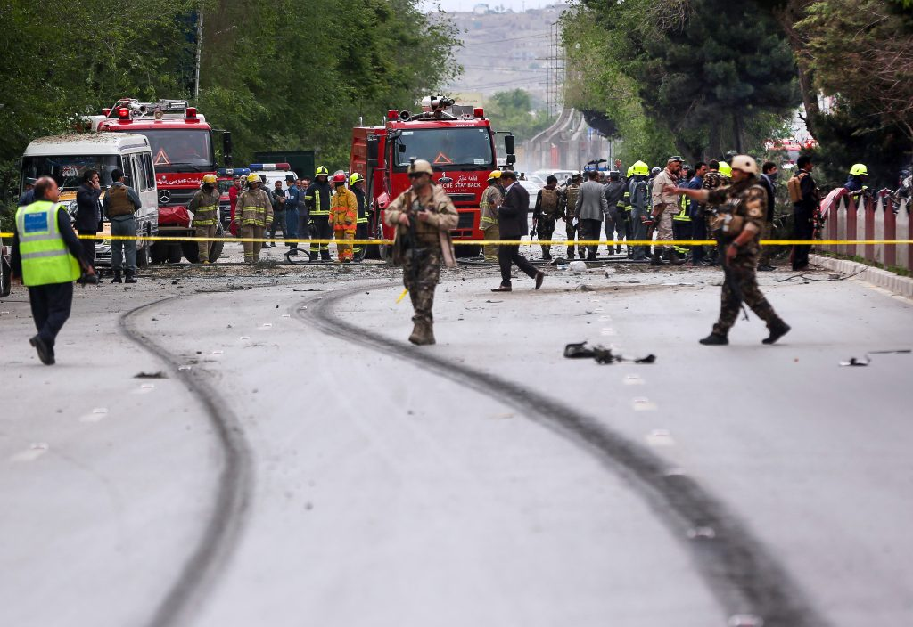 Emergency workers on road in bomb aftermath (© AP Images)
