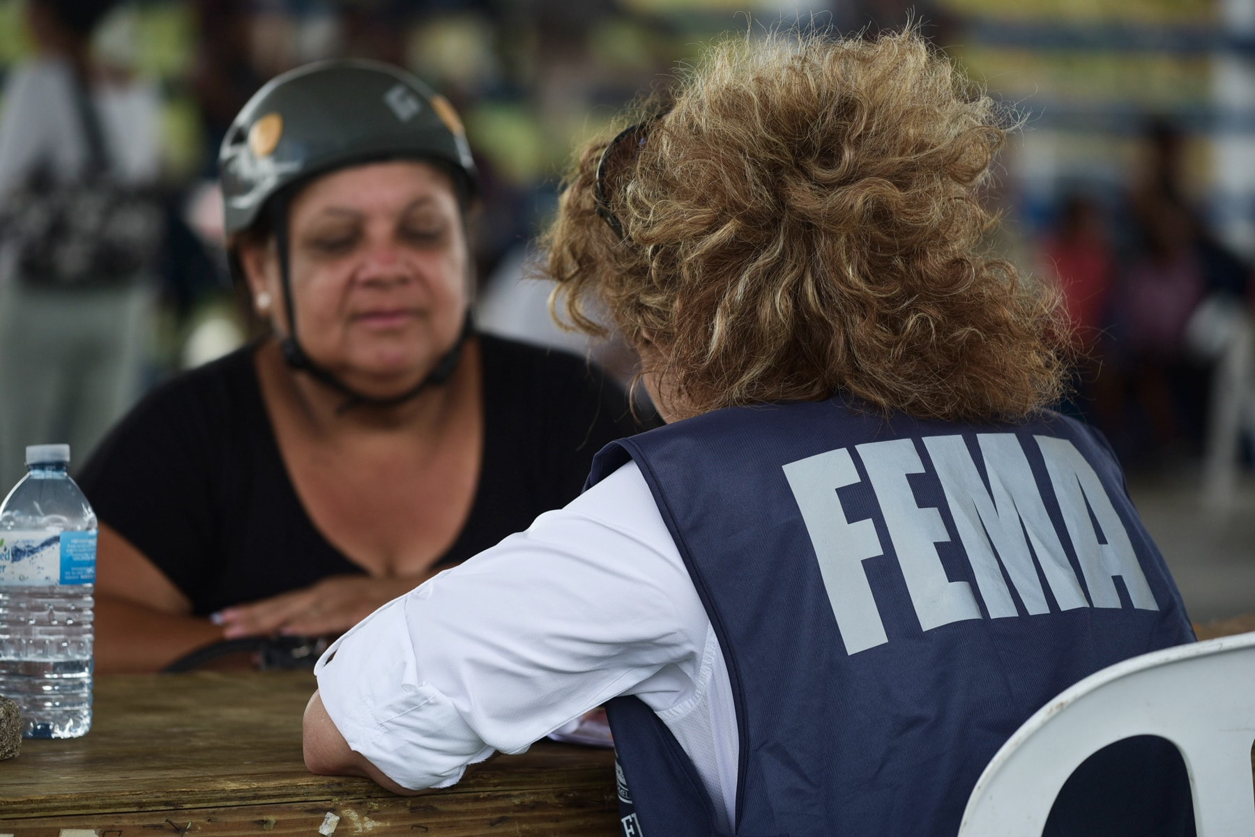 Two people sitting across table, one wearing FEMA vest (© AP Images)