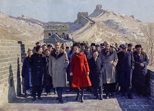 Richard Nixon and Pat Nixon walking along Great Wall with large group of people (© AP Images)