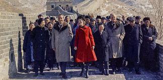Richard Nixon and Pat Nixon walking along Great Wall with large group of people (© AP Images)