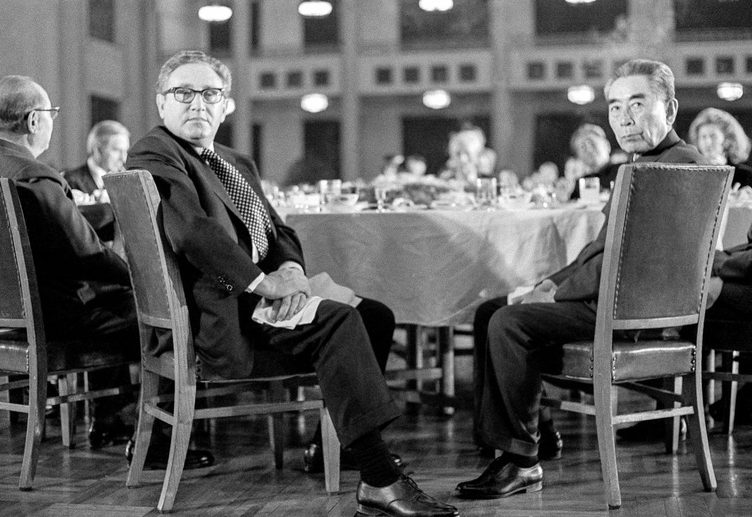 Henry Kissinger and Zhou Enlai seated at table with others (© AP Images)