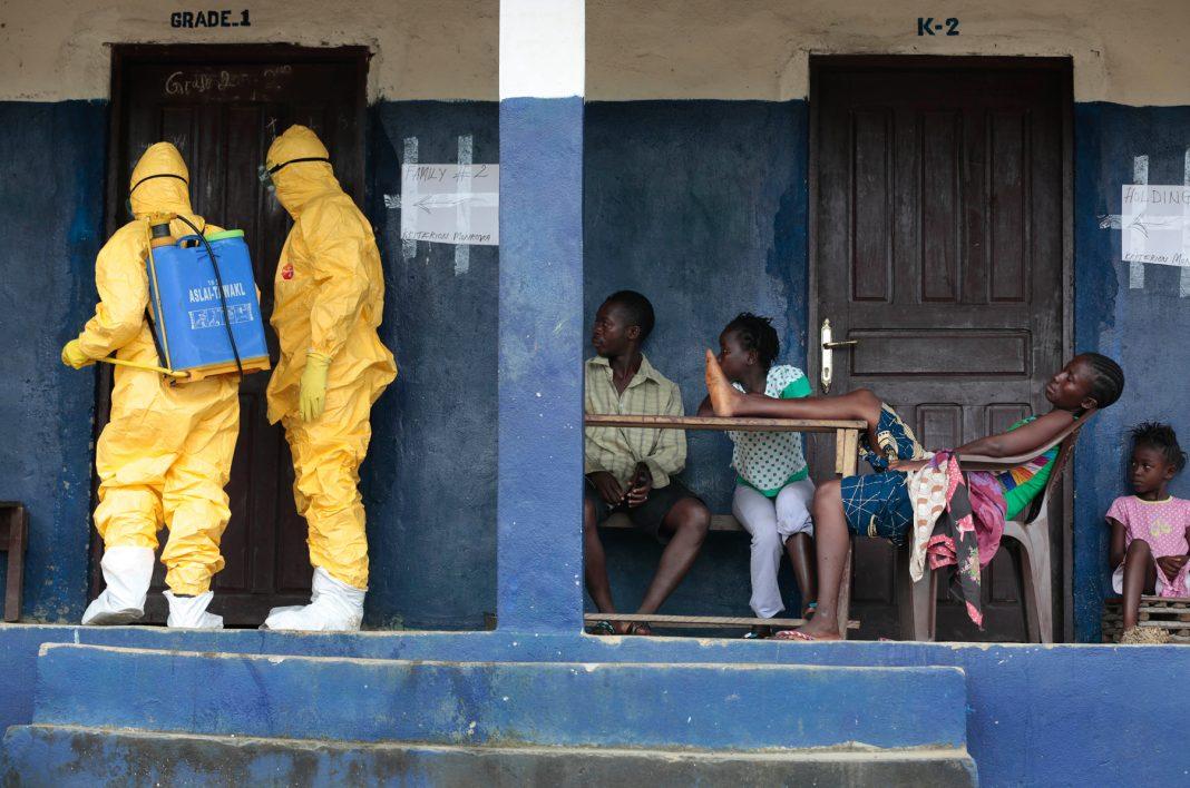چار افراد حفاظتی لباس پہنے دو افراد کو ایک گھر کے دروازے پر کھڑا دیکھ رہے ہیں۔ (© AP Images)