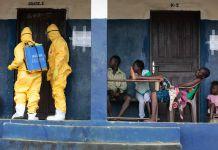 Cuatro personas observan a dos personas en traje de protección frente a una puerta (© AP Images)