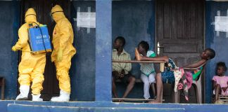 Four people watching two people in hazmat suits at a door (© AP Images)