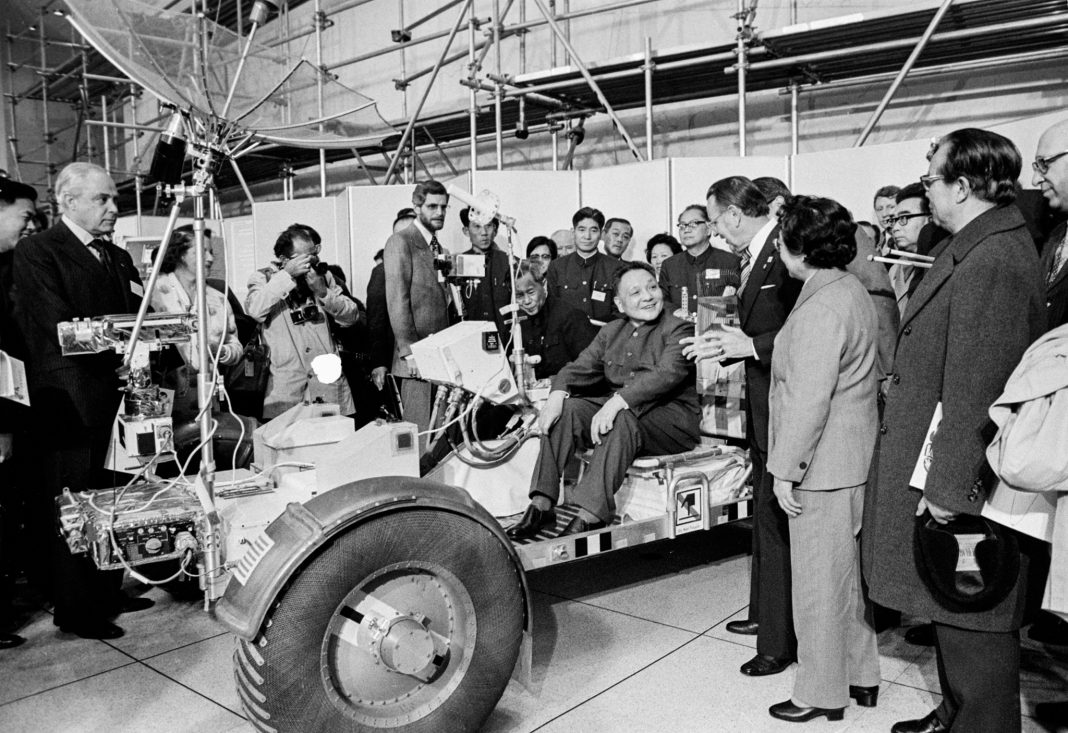 Man sitting in lunar rover vehicle with crowd around him (© AP Images)