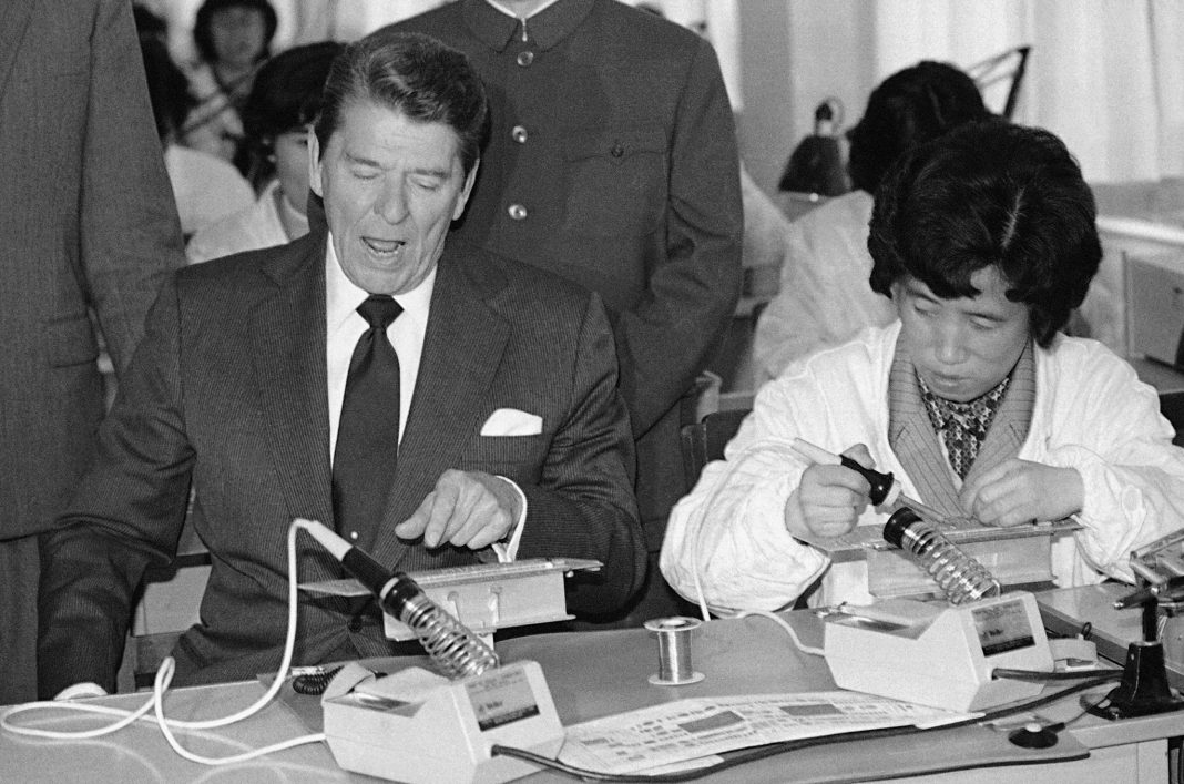 President Reagan sitting next to woman working on electronic device (© AP Images)