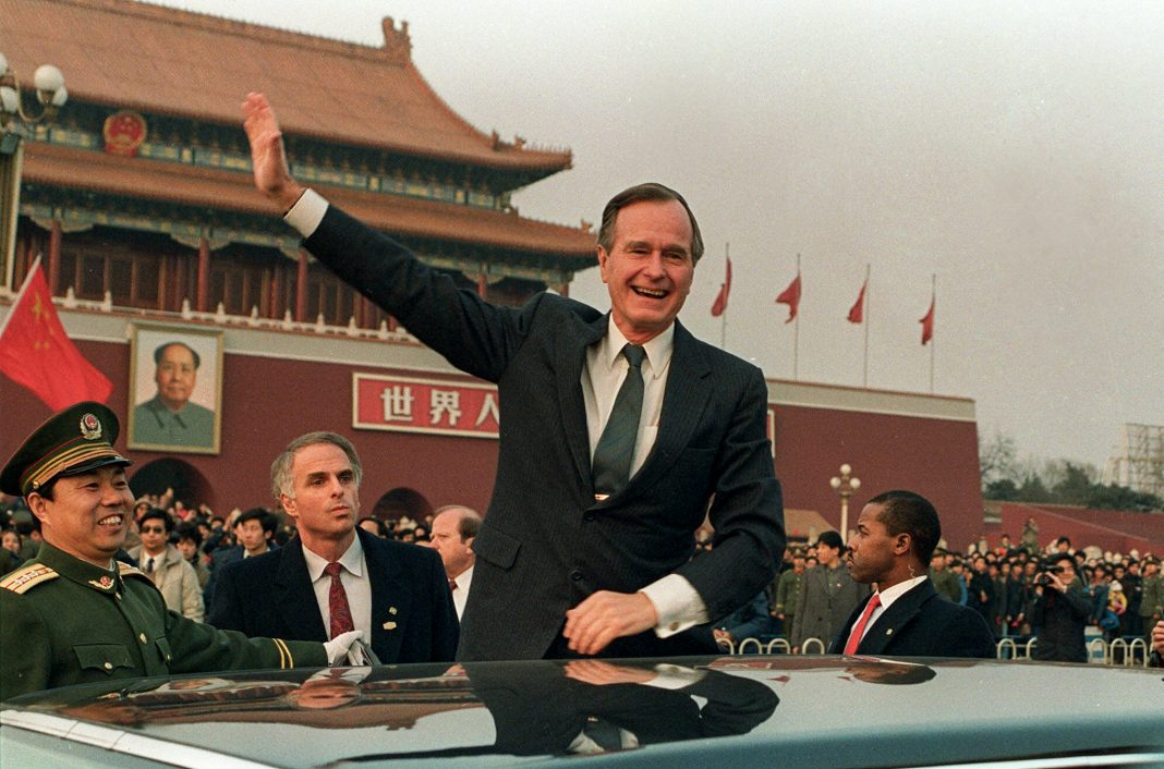 George H.W. Bush waving from next to car (© AP Images)