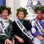 Bill Rodgers, Greta Waitz and Alberto Salazar wearing laurel wreaths and name sashes (© AP Images)