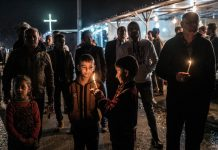 Adults and children with candles and crosses standing outside at night (© AP Images)