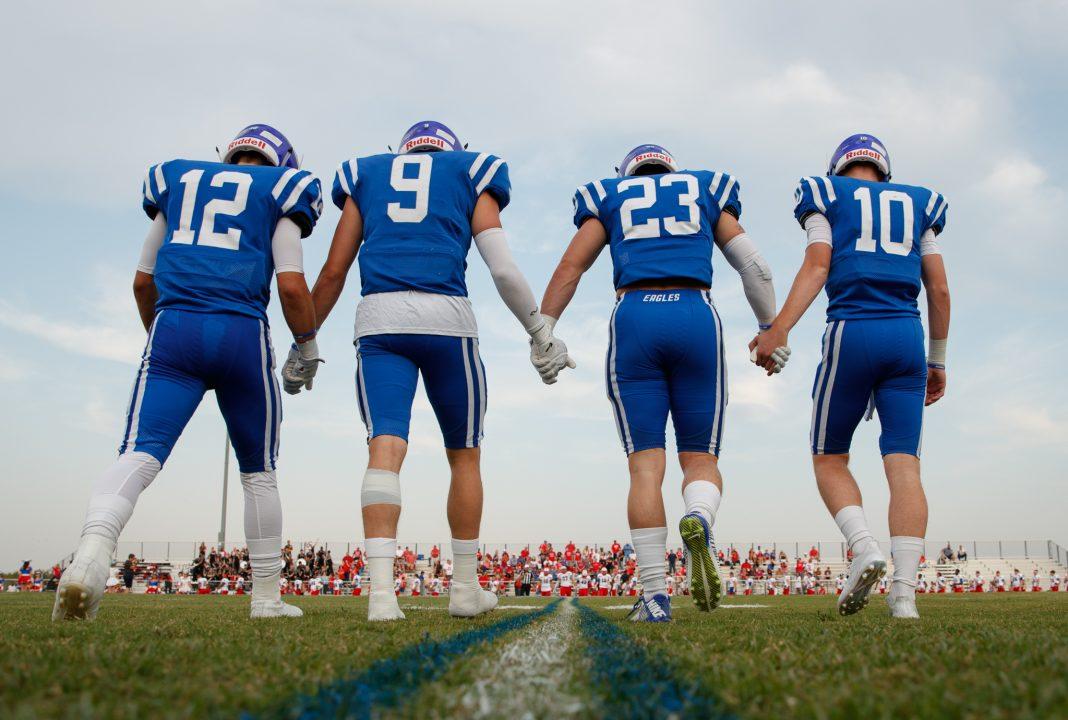 Cuatro jugadores de fútbol americano tomados de la mano en el campo, mirando a los seguidores sentados en las bancas (© Tim Richardson)