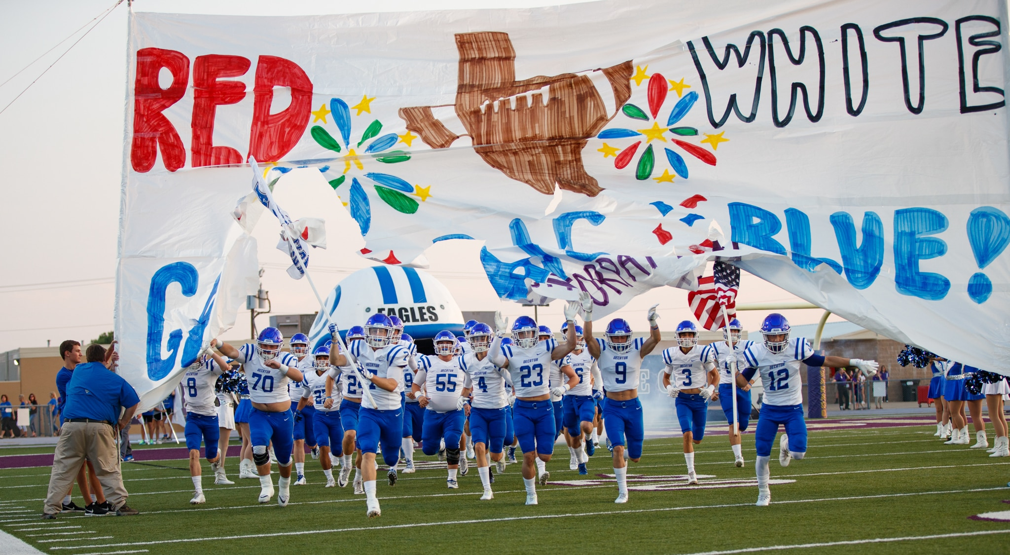 Football players running through large team sign onto playing field (© Tim Richardson)