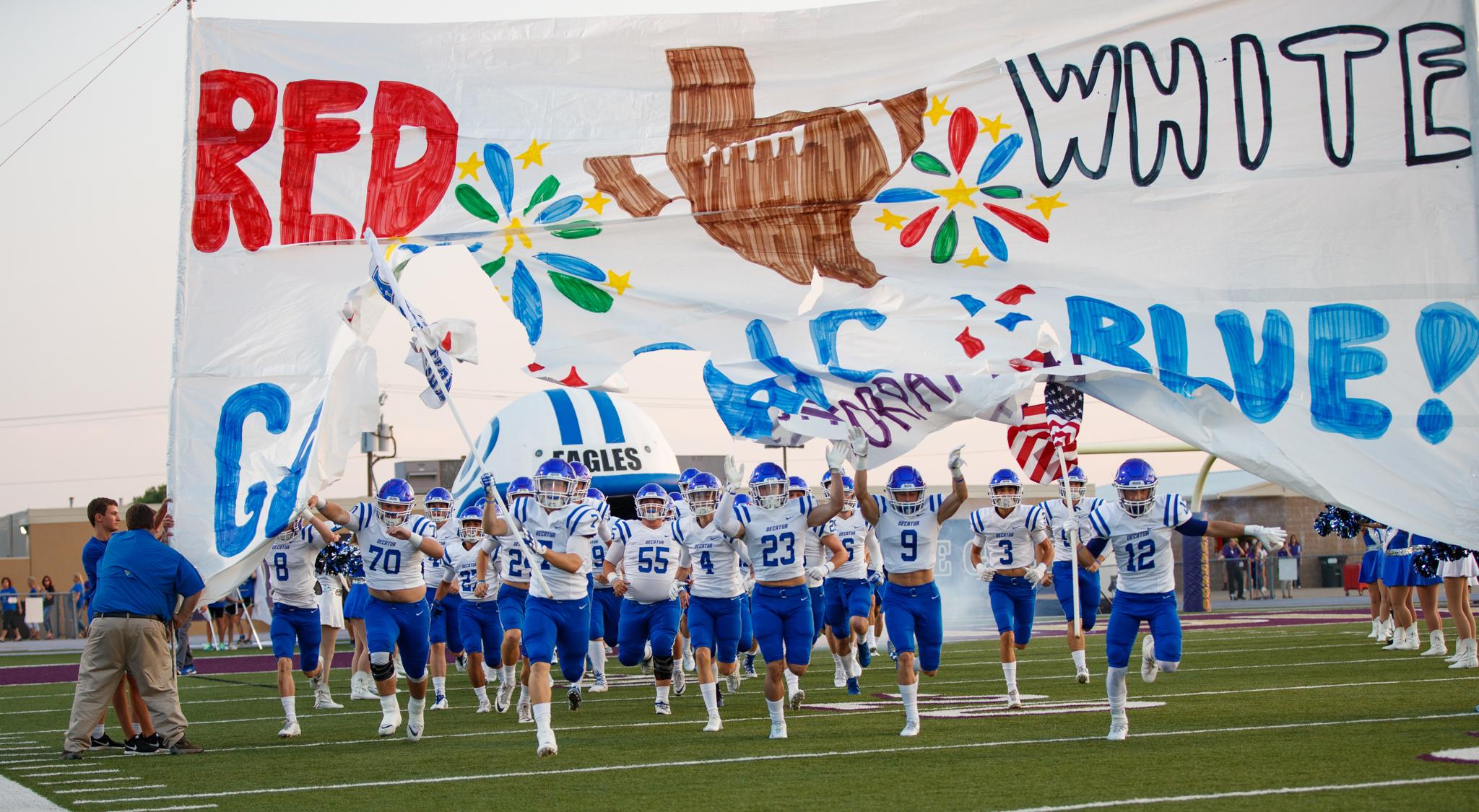 Jugadores fútbol americano atraviesan una gran pancarta corriendo para entrar al campo de juego (© Tim Richardson)