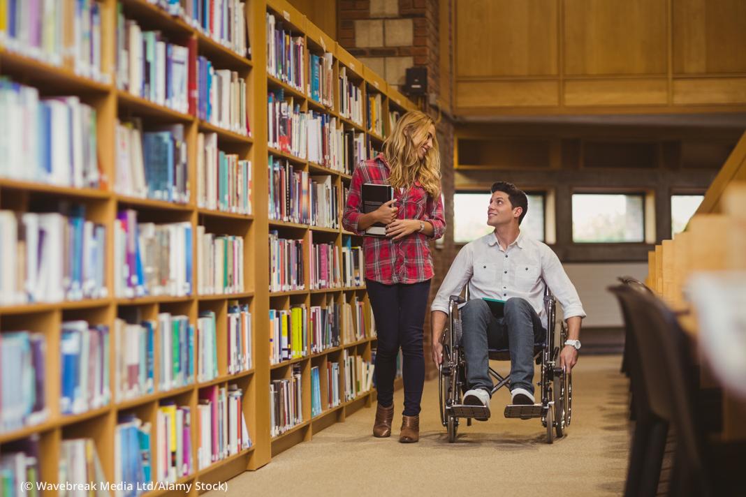 Man in wheelchair talking with woman in library (© Wavebreak Media Ltd./Alamy Stock)