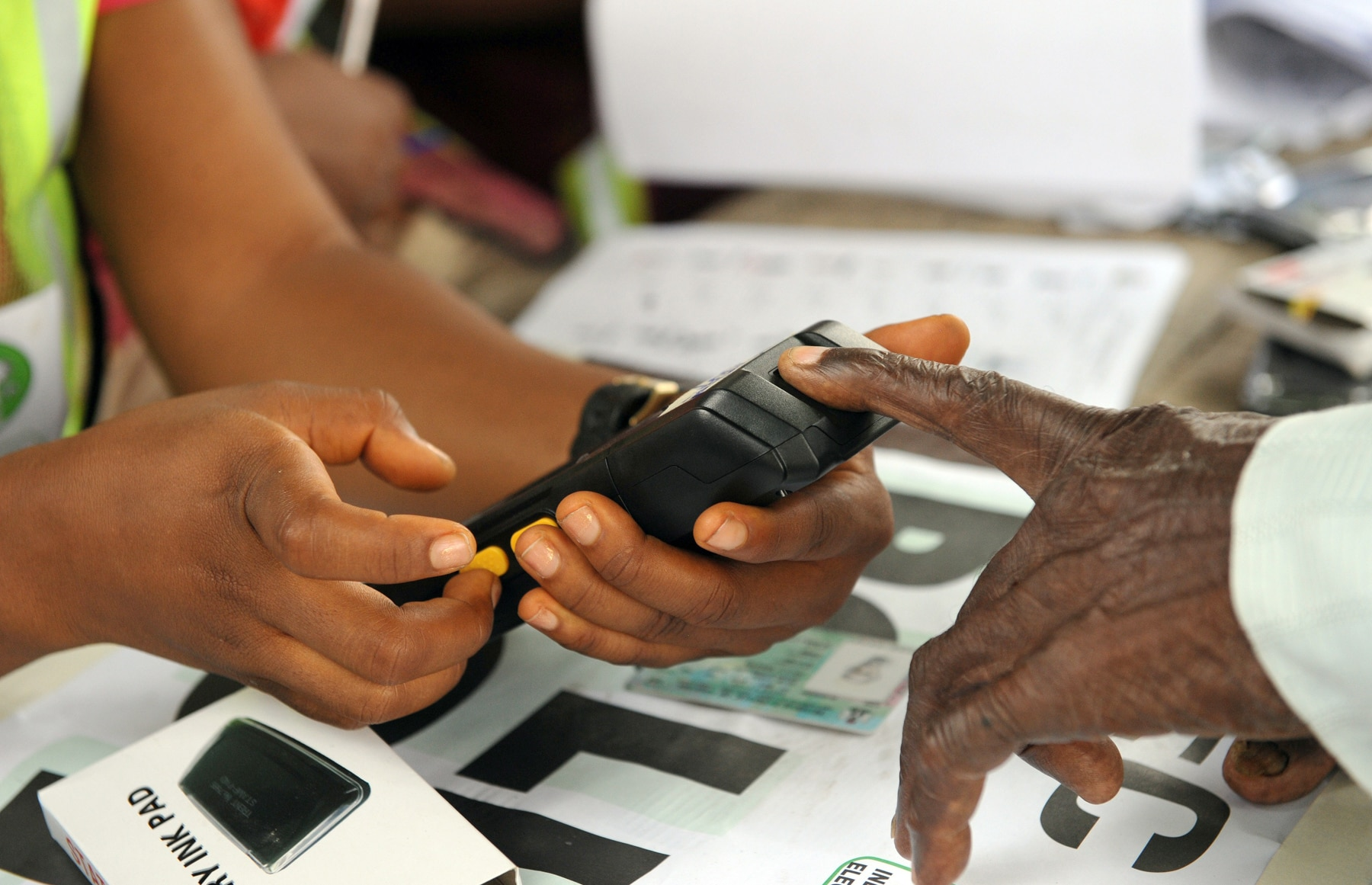 Person placing finger on handheld machine (© Pius Utomi Ekpei/AFP via Getty Images)