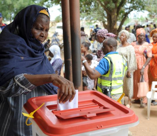 Woman dropping vote in ballot box with line of people behind her (© Pius Utomi/AFP via Getty Images)