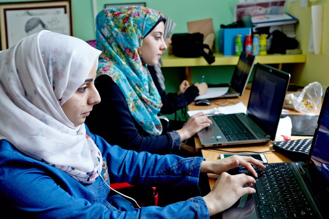 Women wearing headscarves working at computers (© Shawn Baldwin/Bloomberg via Getty Images)