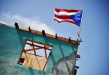 Puerto Rico flag flying atop a damaged building (Hector Retamal/AFP via Getty Images)