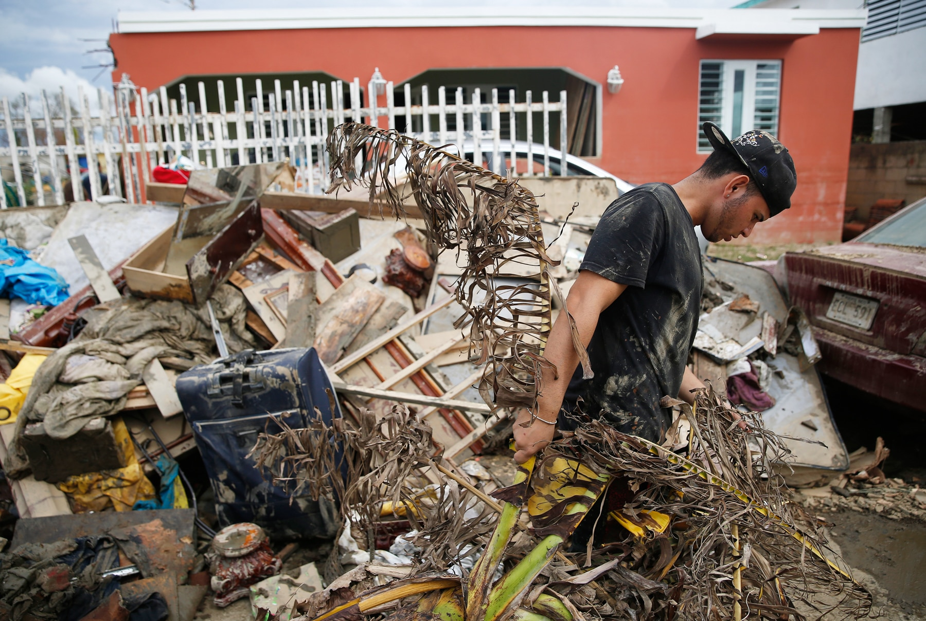 Man walking past pile of debris outside house in Puerto Rico (© Jessica Rinaldi/The Boston Globe via Getty Images)