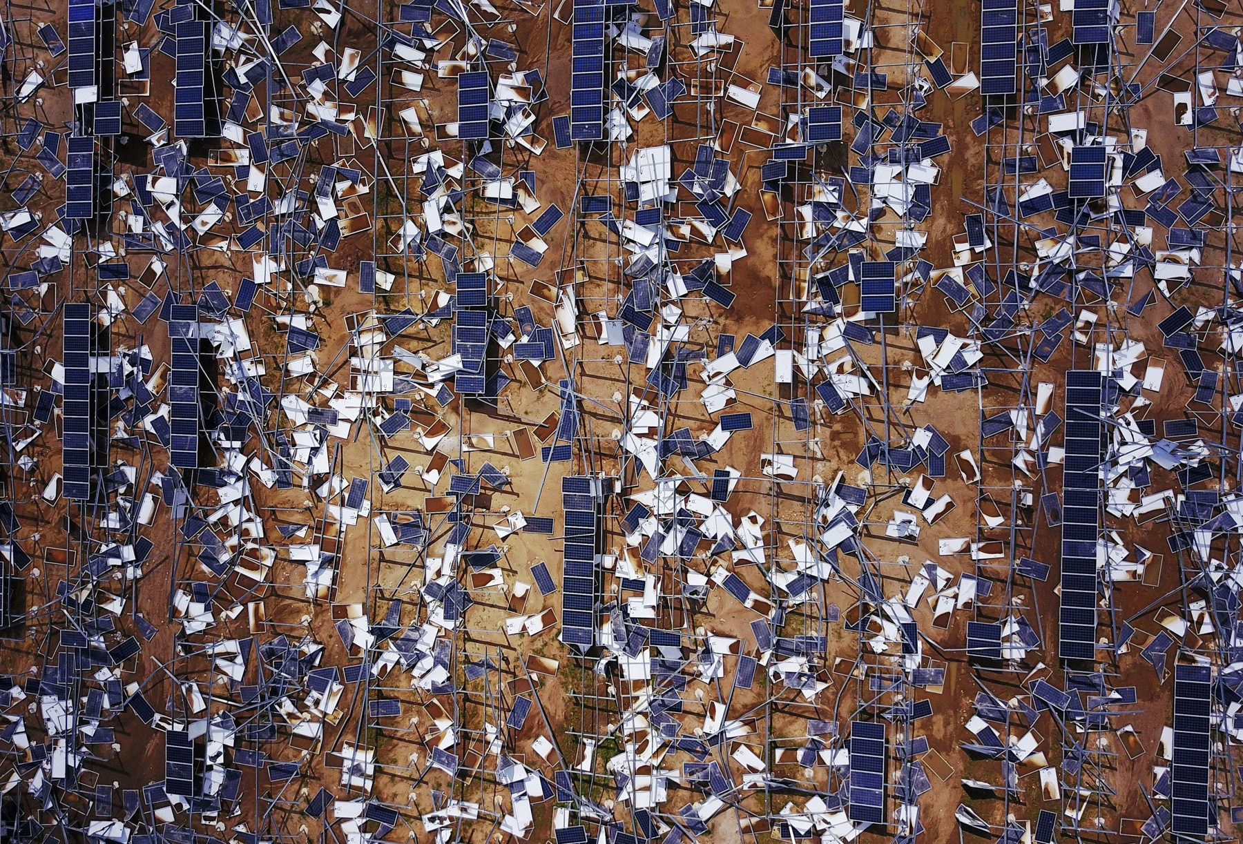 Aerial view of damaged solar panels scattered in field in Puerto Rico (© Ricardo Arduengo/AFP via Getty Images)