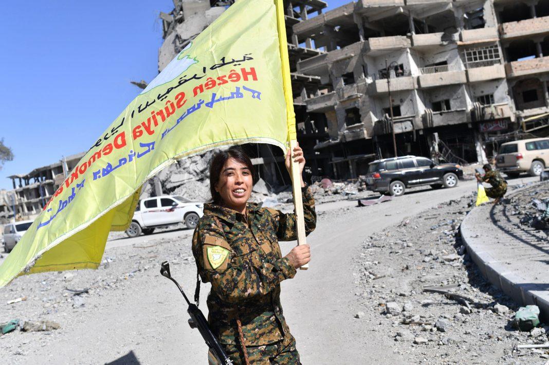 Una mujer combatiente sostiene un estandarte amarillo (© Bulent Kilic/AFP vía Getty Images)