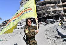 زرد رنگ کا پرچم تھامے ہوئے، ایک خاتون جنگجو۔ (© Bulent Kilic/AFP via Getty Images)