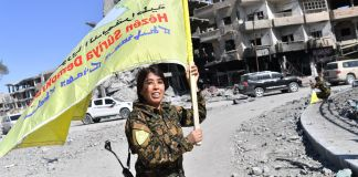 امرأة مقاتلة تحمل راية صفراء (© Bulent Kilic/AFP via Getty Images)