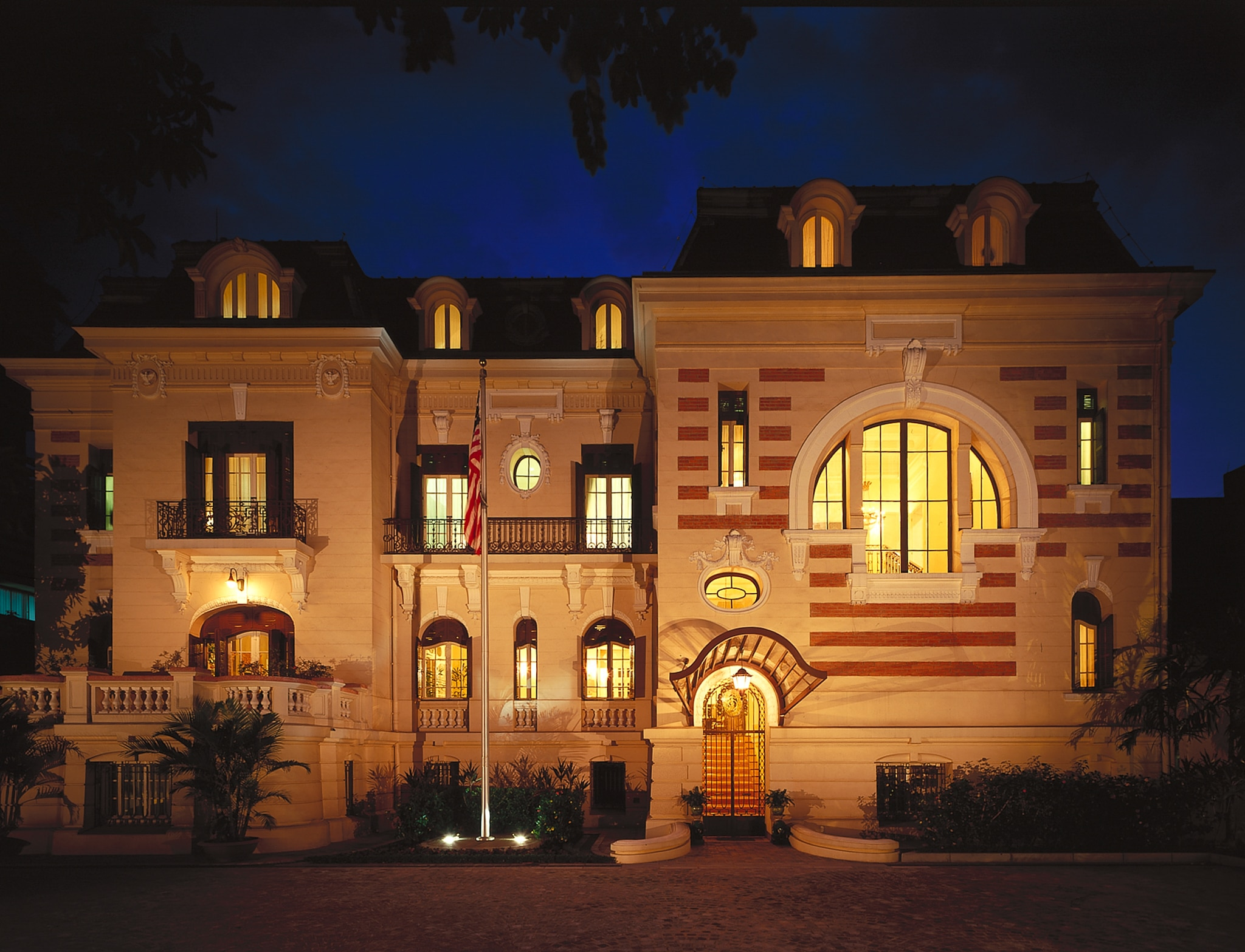Tampilan bangunan malam hari dengan jendela tinggi dan sempit dan garis horisontal di fasad (State Dept.)