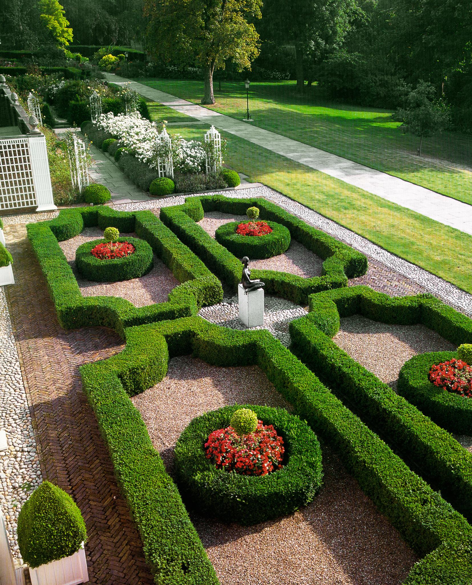 Patung yang dikelilingi pagar tanaman dipangkas dengan pola dekoratif dan jalan setapak (State Dept.)