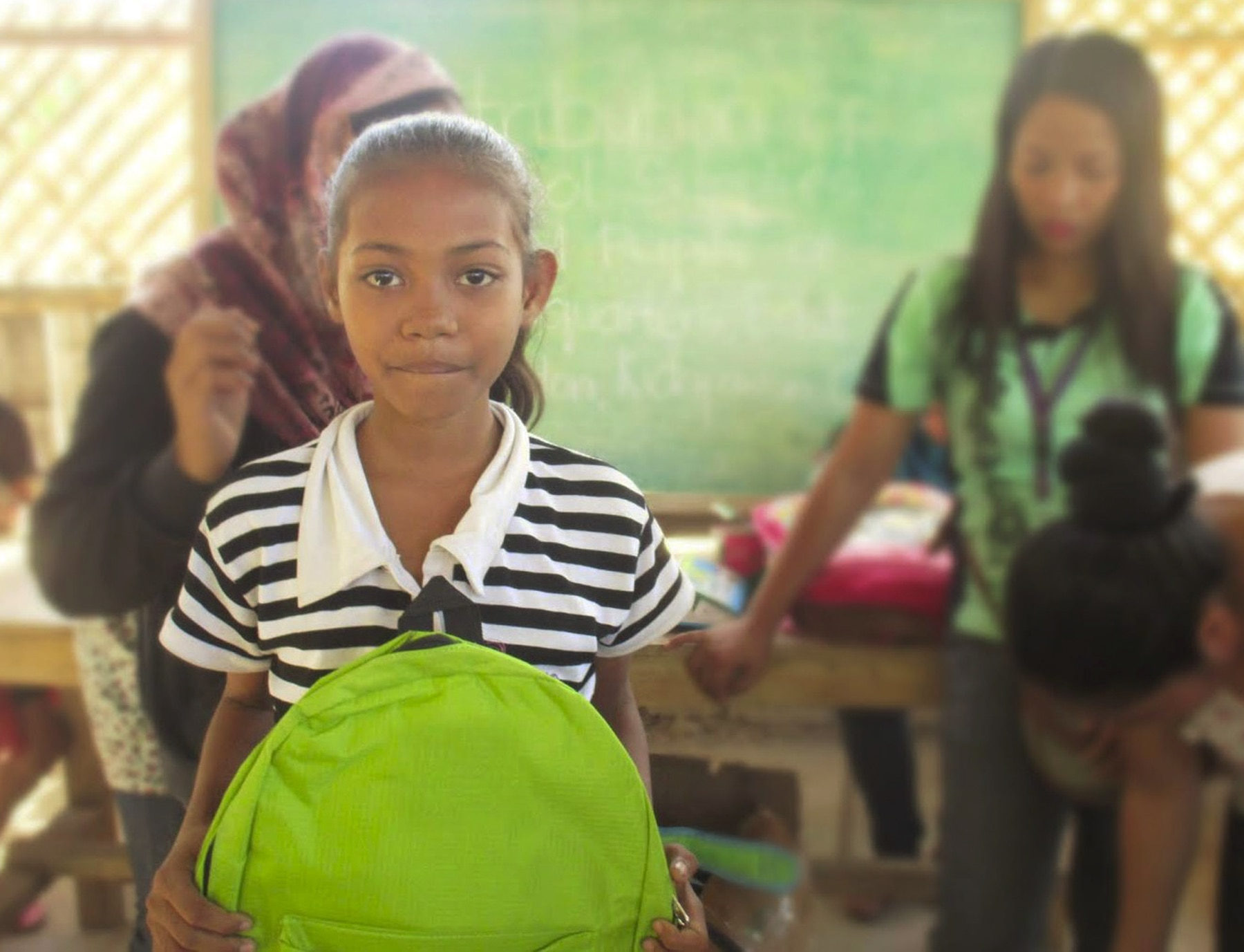 Girl holding green backpack in classroom (Integrated Mindanaoans Association for Natives for USAID)