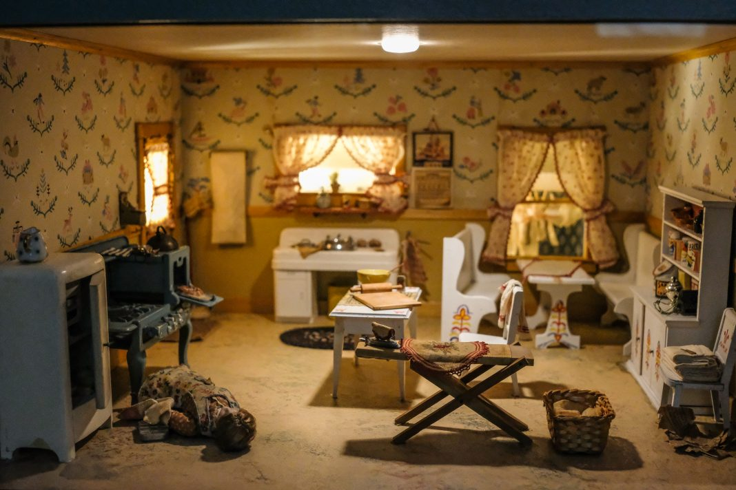 Scène miniature d'une femme morte, allongée sur le sol d'une cuisine (Département d'État/S. L. Brukbacher)