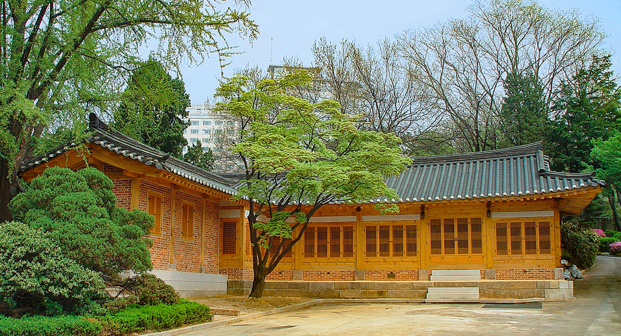 Building with with sloping Asian roof, brick walls and tall, wood-framed windows (State Dept.)