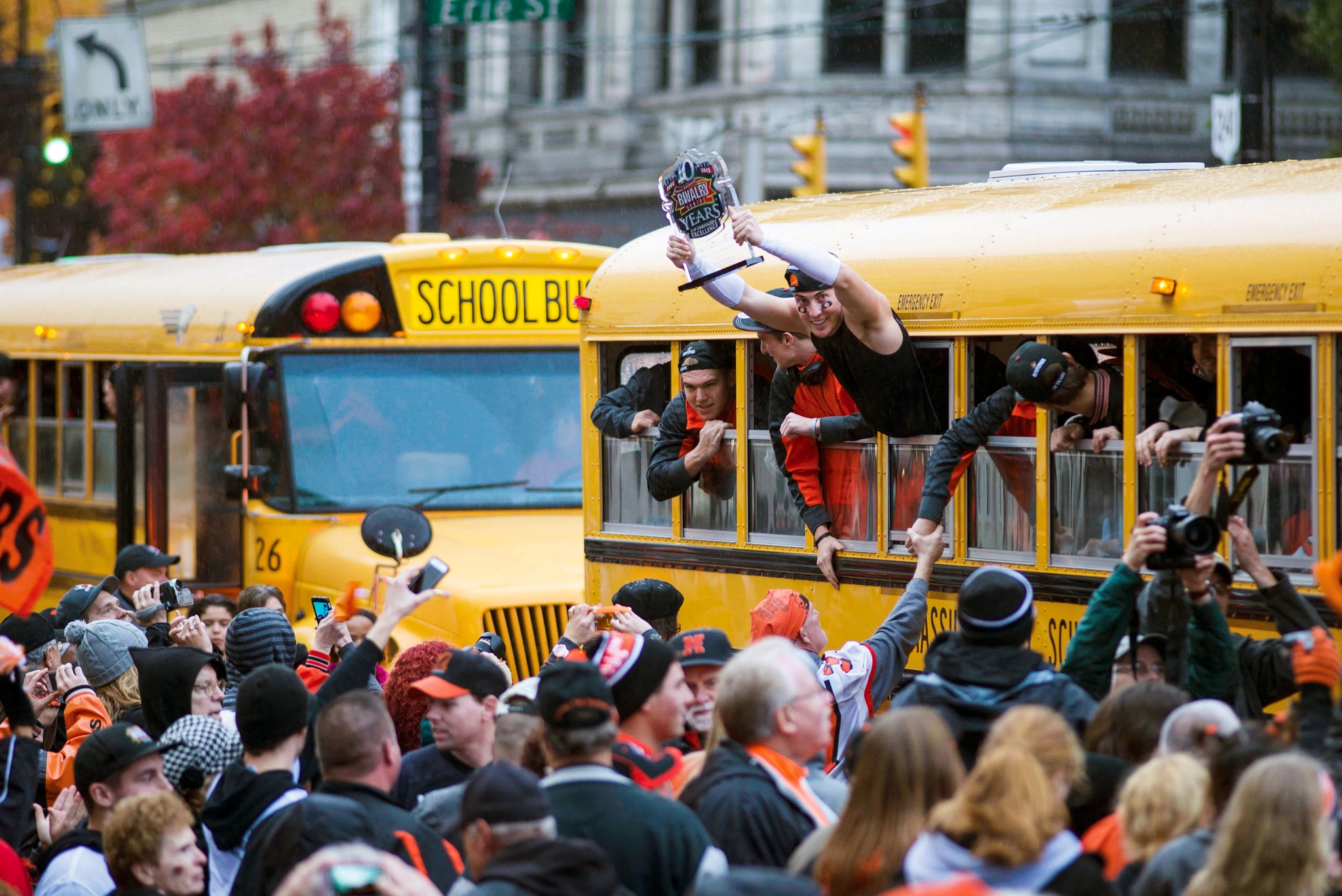 Large crowd around two school buses with people hanging out the windows (© Jenna Watson/Tiger Legacy/Daylight Books)