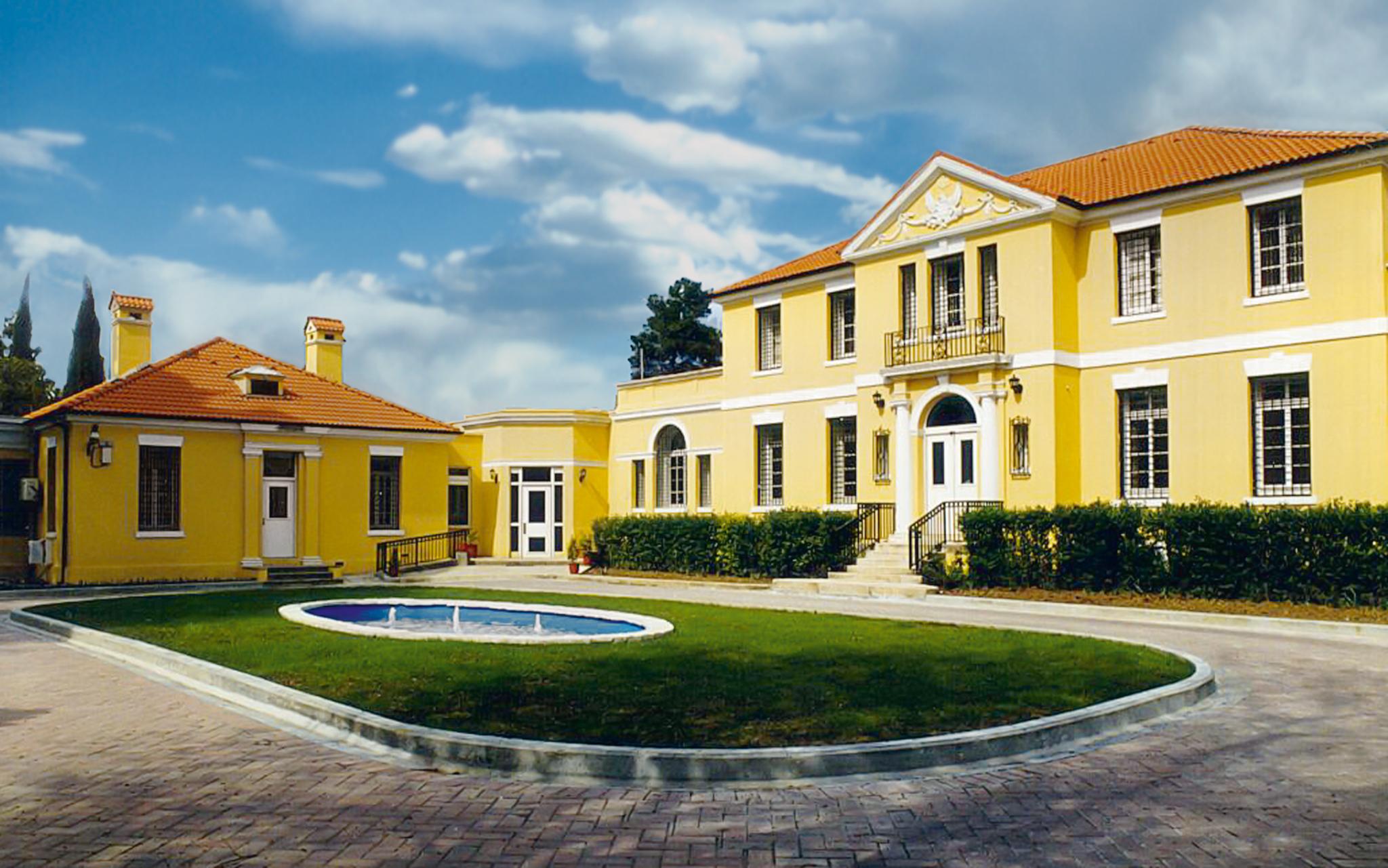 Bangunan berwarna kuning mengelilingi oval berumput dengan air mancur (State Dept.)