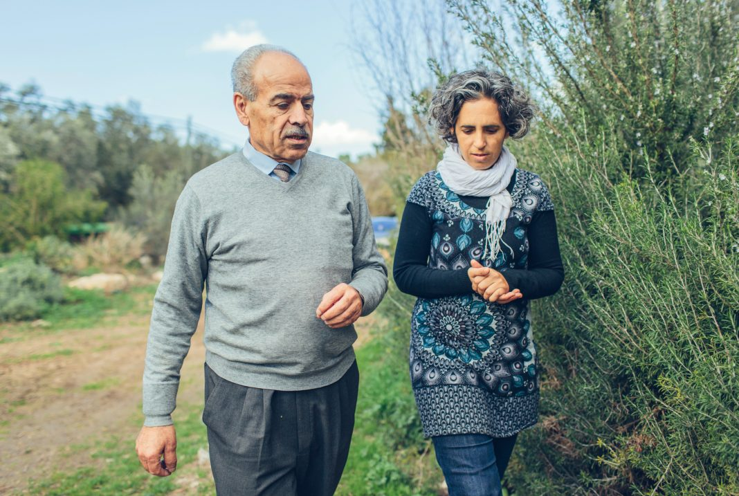Man and woman walking alongside olive grove (USAID/Bobby Neptune)