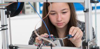 Une jeune fille en train de bricoler sur une machine avec un tournevis (©Shutterstock)