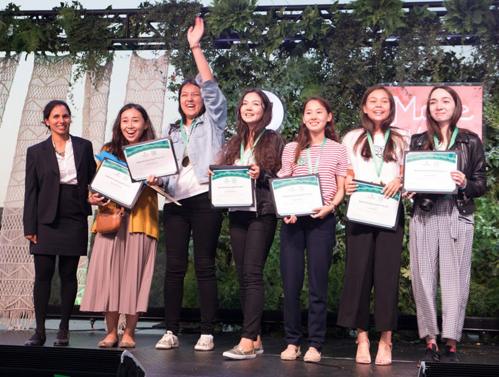 Six teenagers holding winners' certificates on a stage with a woman (Photo by Iridescent)