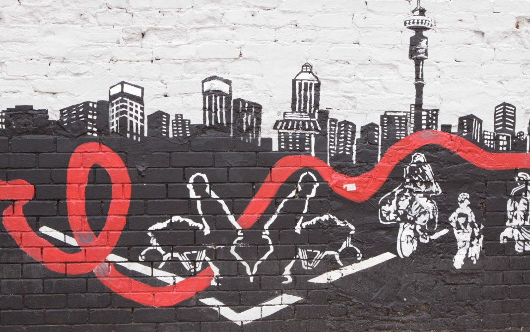 Mural showing city with people and red ribbon running through it (© AP Images)