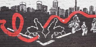 Mural mostra cidade com pessoas e fita vermelha representando a Aids (© AP Images)