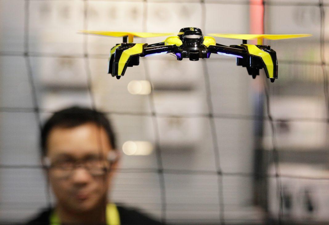 Hombre observando un aparato teledirigido que vuela (© AP Images)