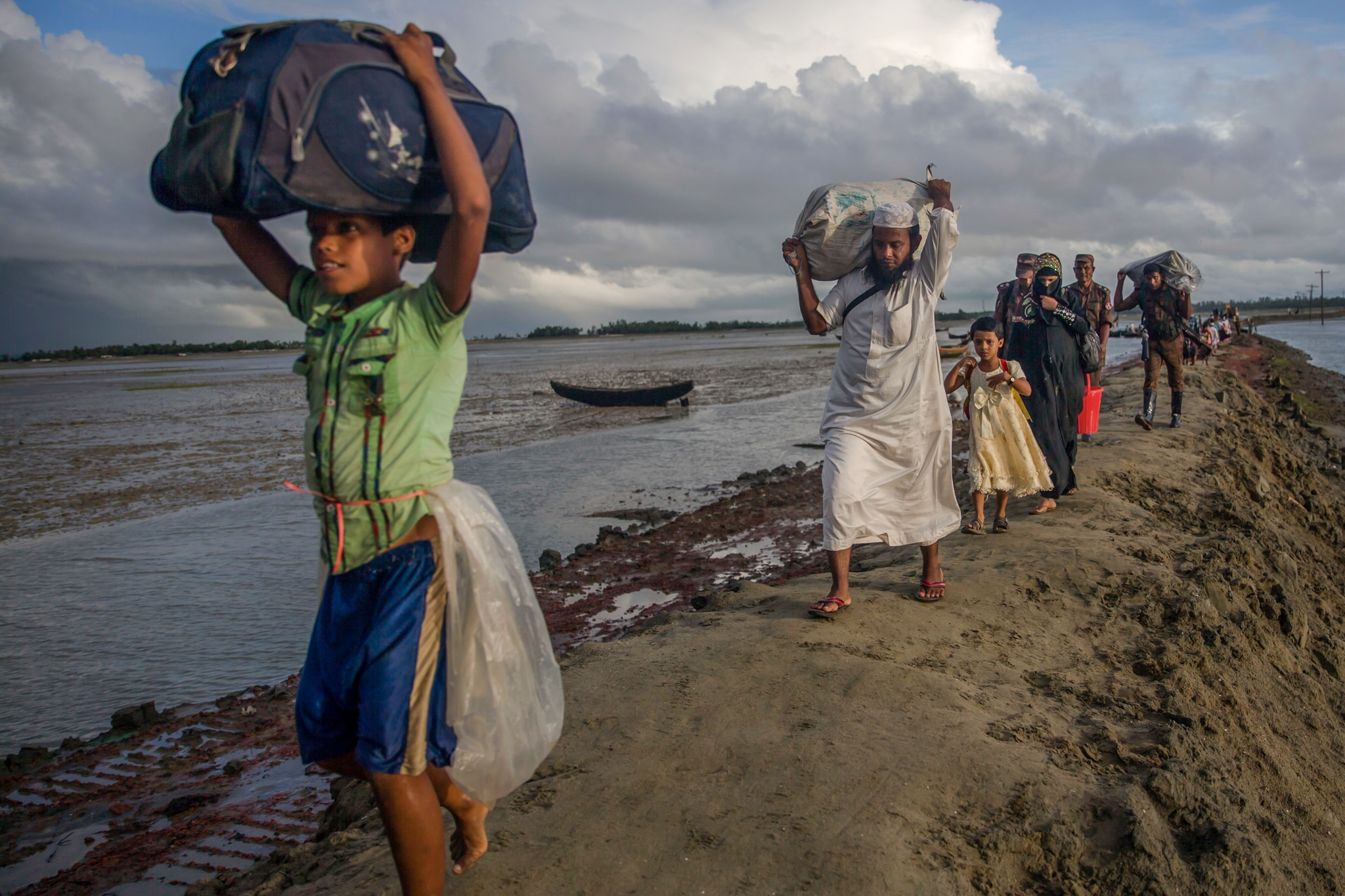 Refugees walking alongside water carrying large bundles of belongings (© AP Images)