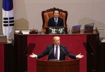 Presidente Trump falando na tribuna com uma pessoa sentada em uma mesa mais ao alto e atrás dele (© AP Images)