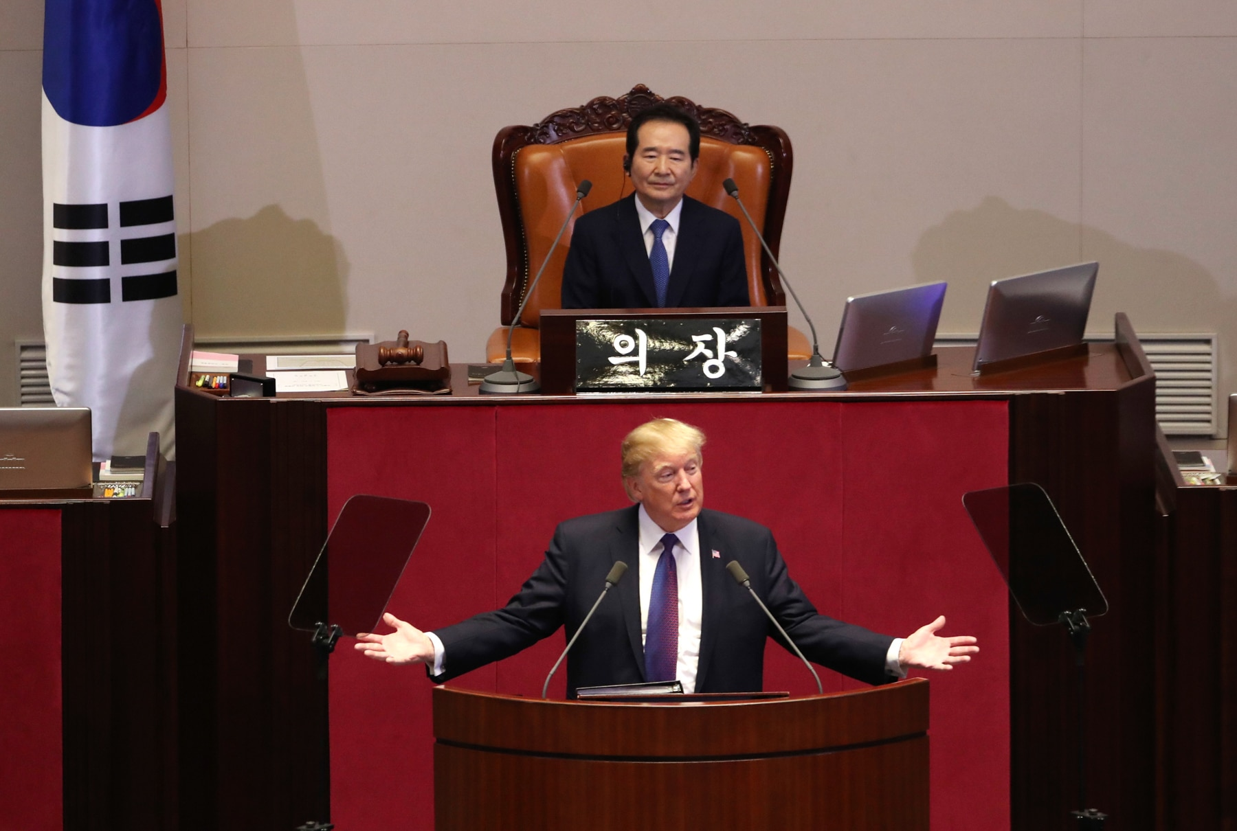President Trump speaking at lectern with person seated above and behind him (© AP Images)