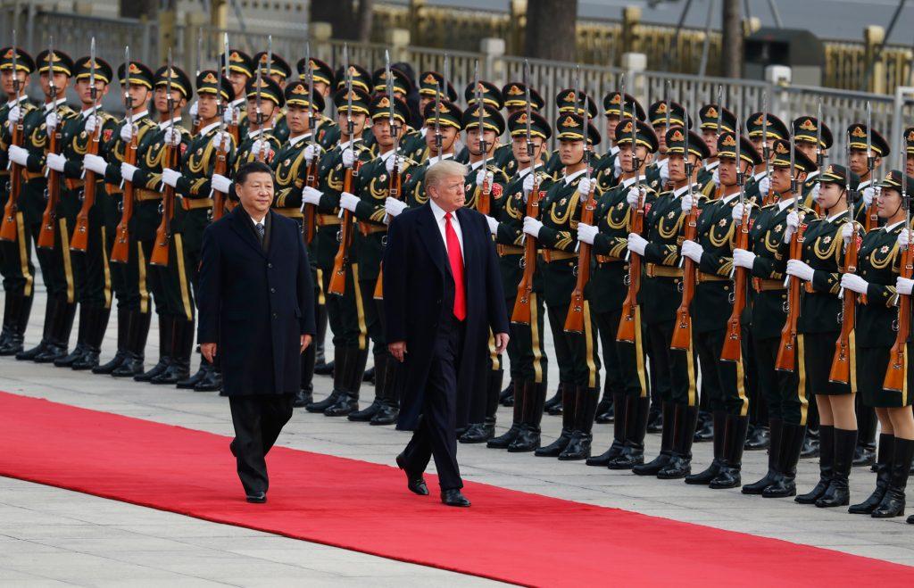 Le président Trump et le président Xi Jinping passant devant des militaires (© AP Images)