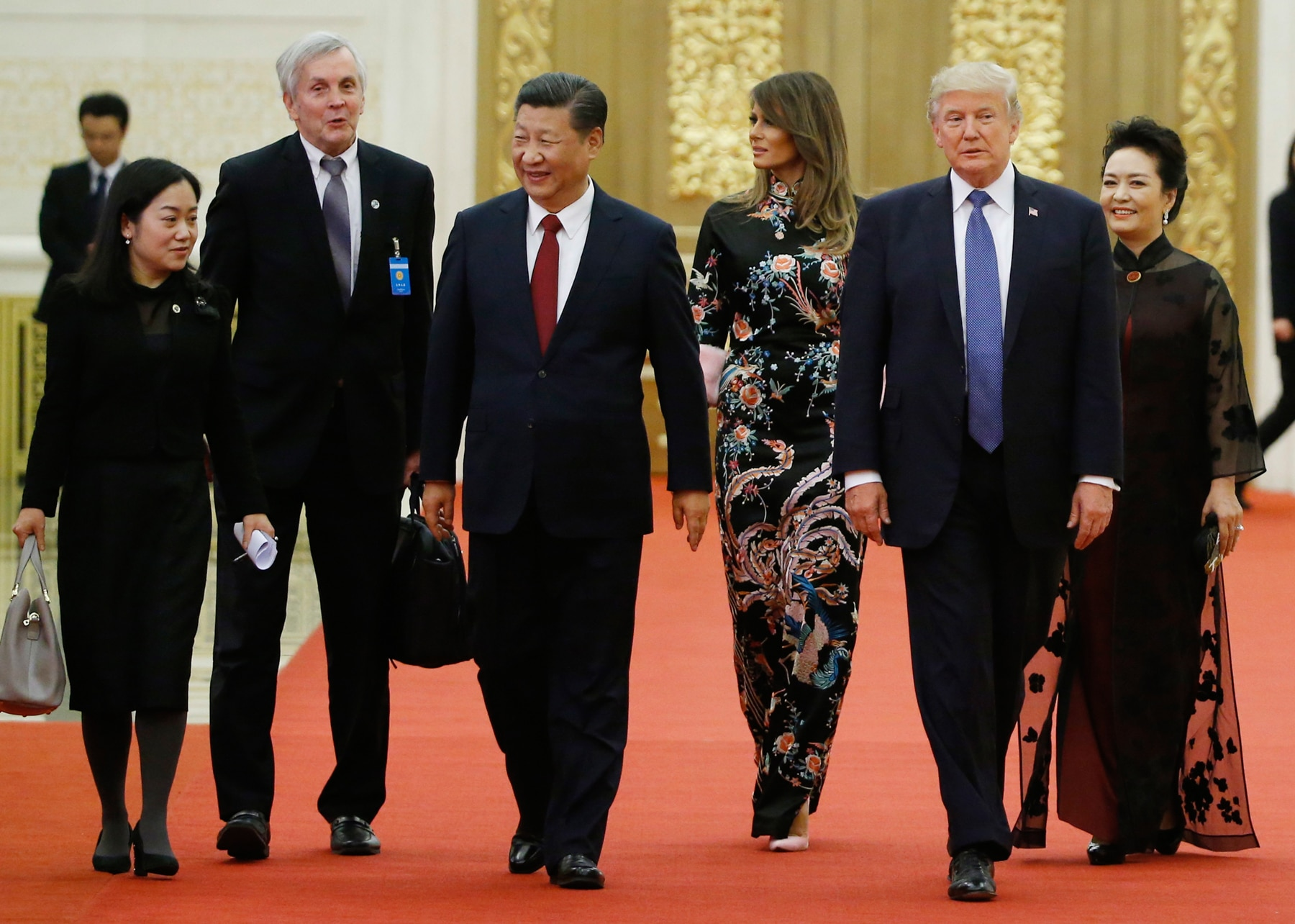 U.S. President Donald Trump and Chinese President Xi Jinping walking on red carpet with their wives (© AP Images)