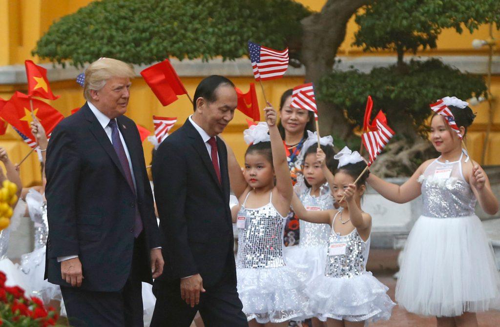 어린이 무용수들이 트럼프 대통령과 쾅 대통령에서 국기들 흔들고 있다 (© AP Images)