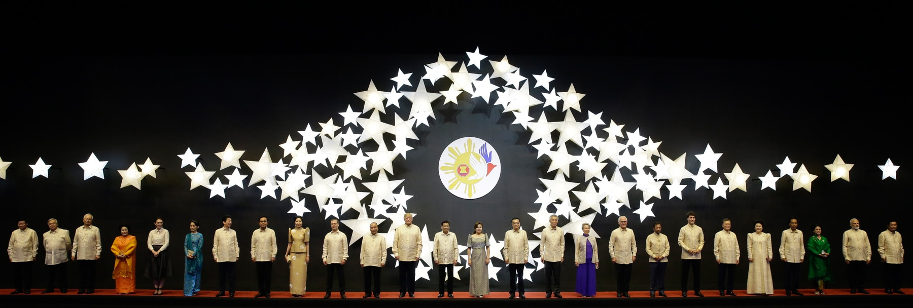 Leaders standing in front of mural of stars (© AP Images)